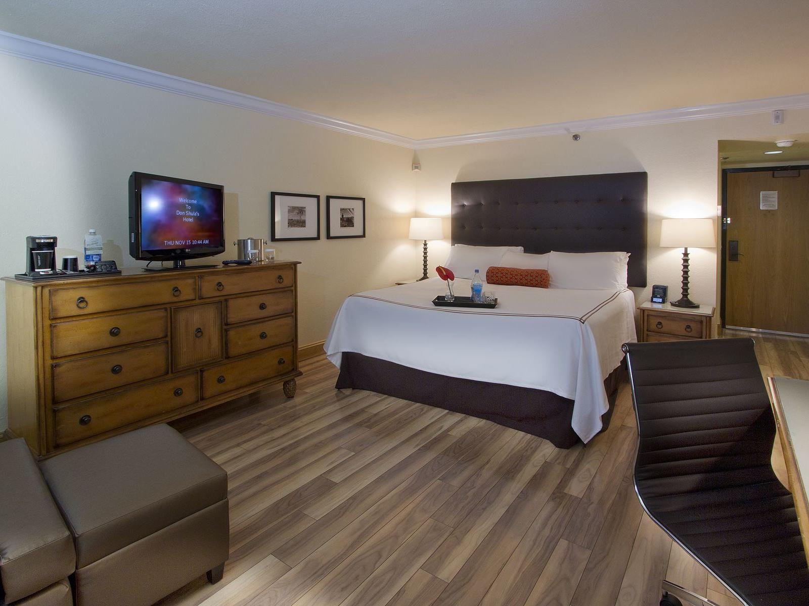 room with king bed, dresser and television