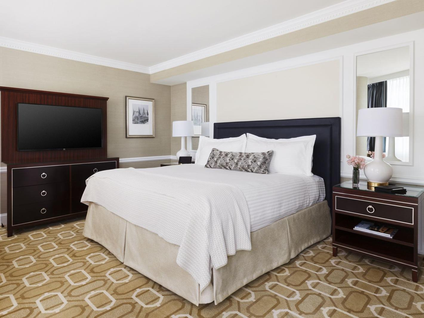 King bed with wall mounted TV above dresser