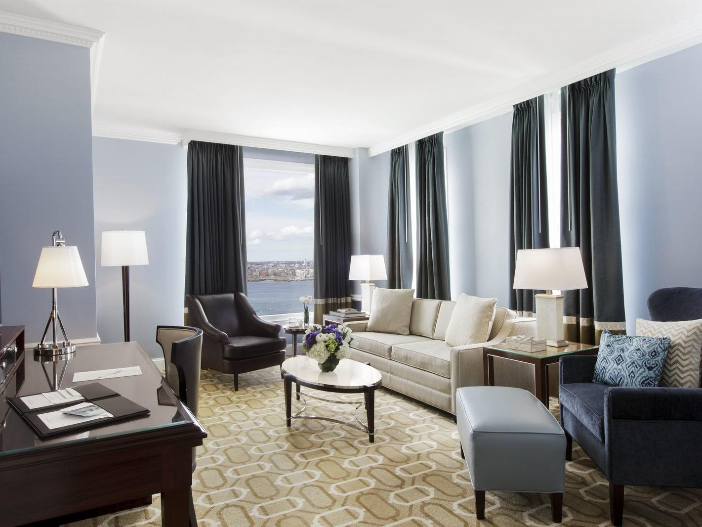 Suite living room with couch, accent chairs and desk with harbor view