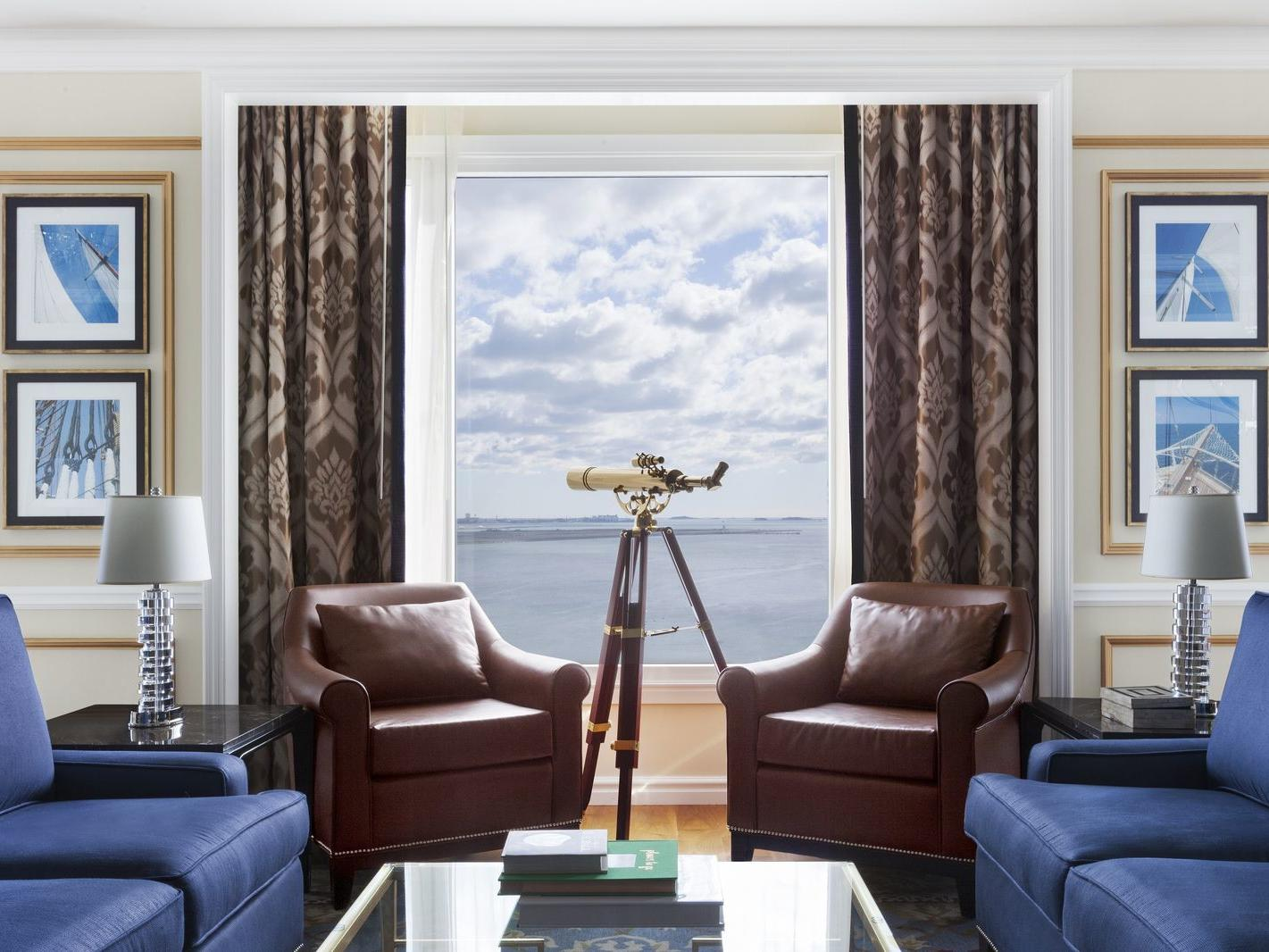 Suite living room with telescope by window with harbor view