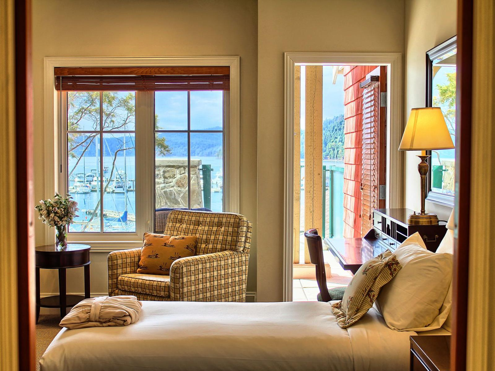 bedroom with door that leads to balcony overlooking ocean