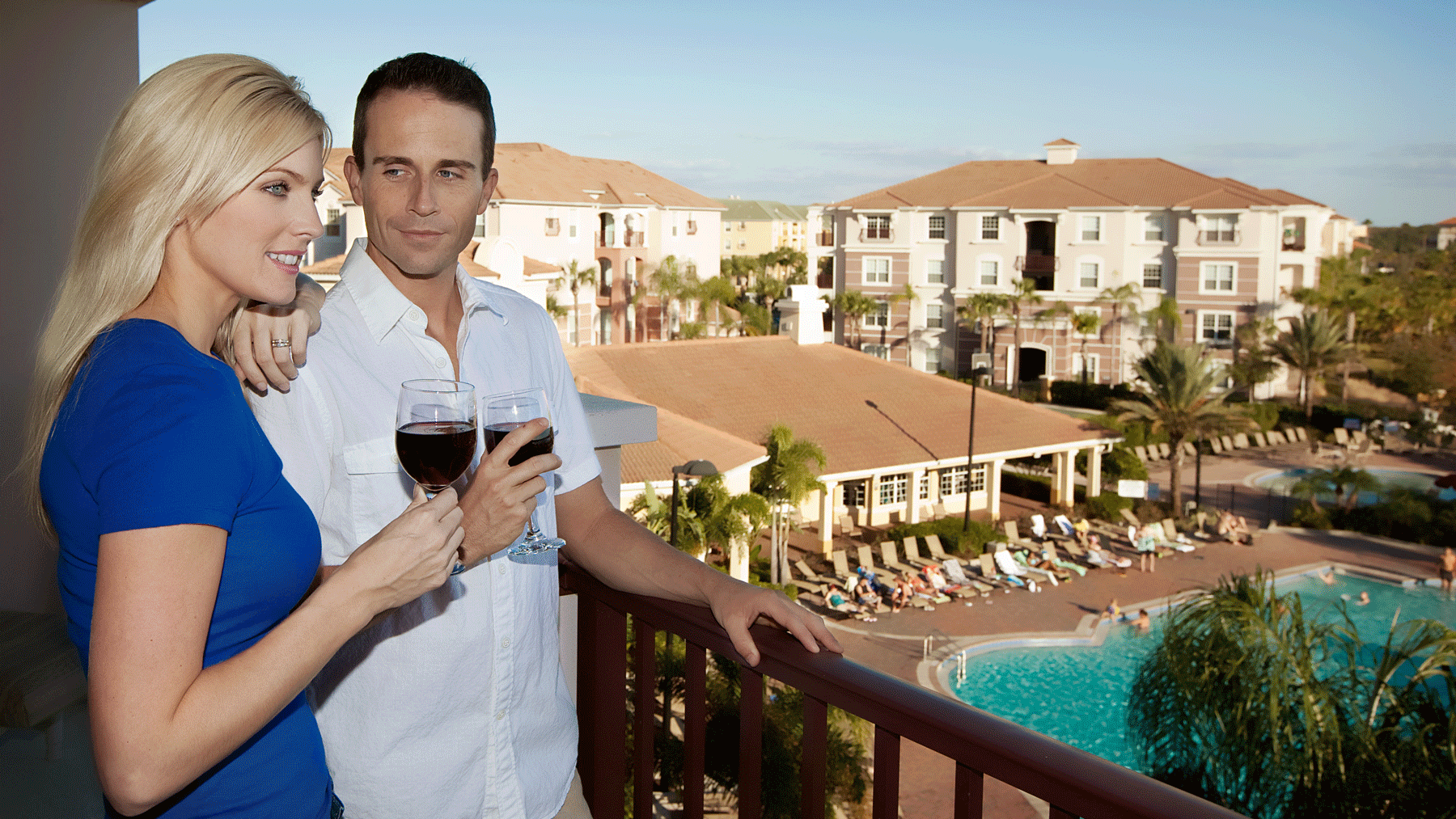 Couple drinking wine on balcony overlooking pool