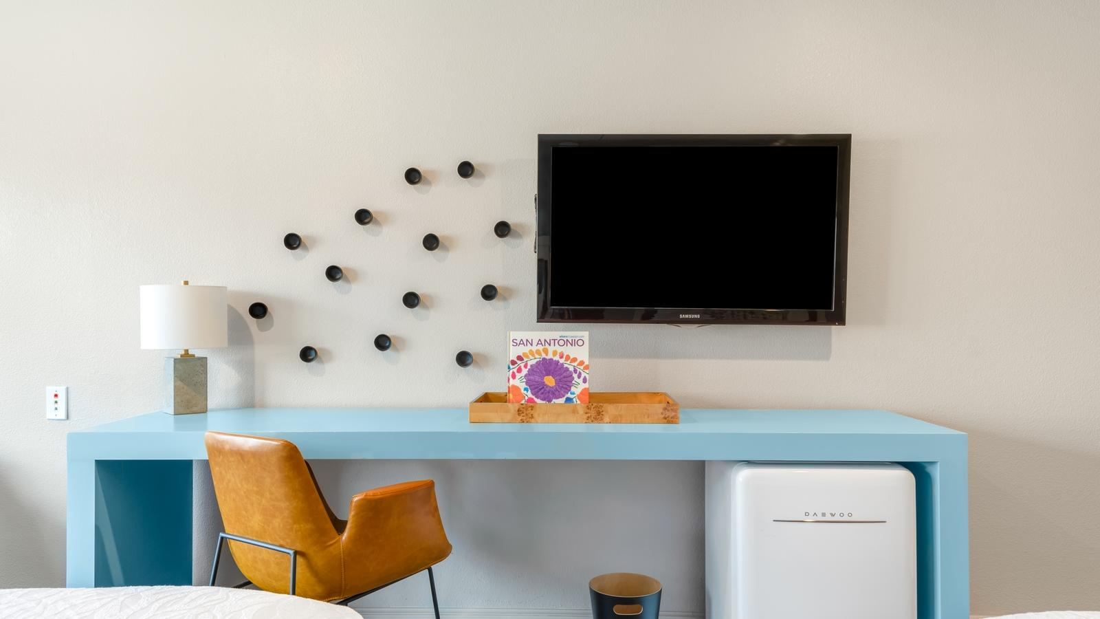 Desk with TV mounted on wall and mini fridge