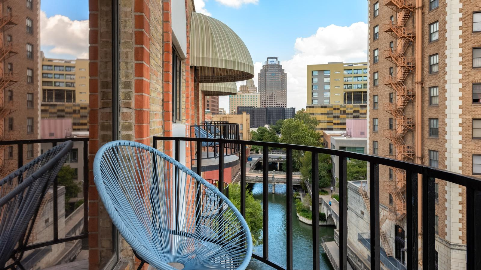 Chair on balcony with view of buildings along river