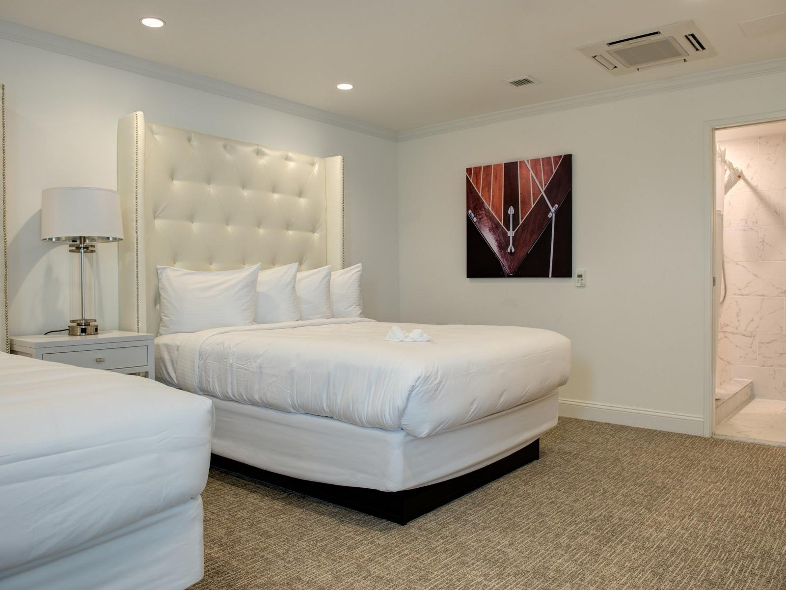 room with two all white beds and tall headboard