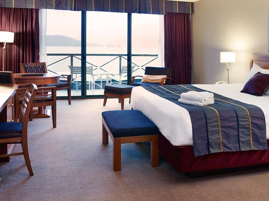 hotel room with balcony overlooking ocean