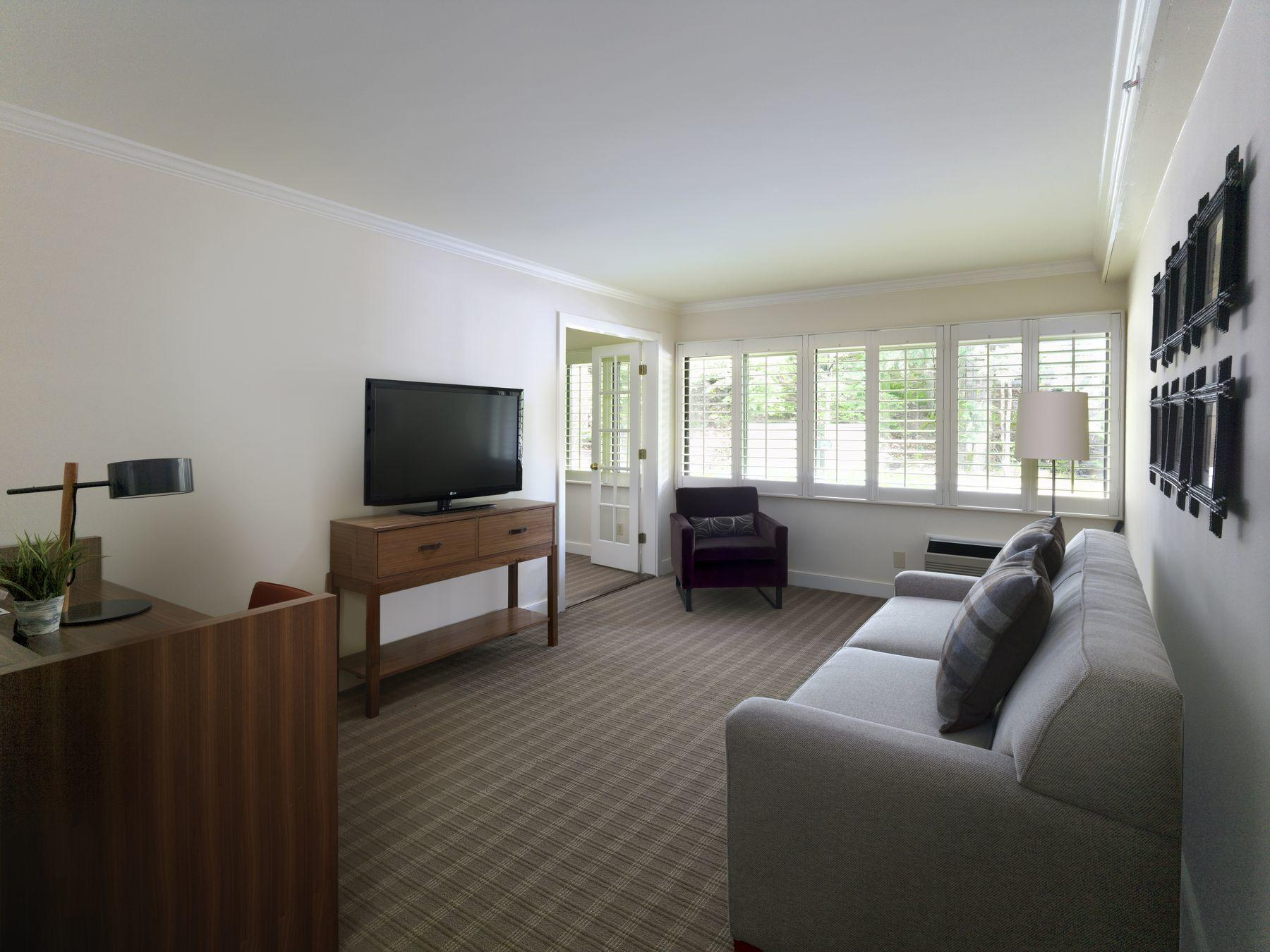 Broad living space of hotel suite with couch and tv.