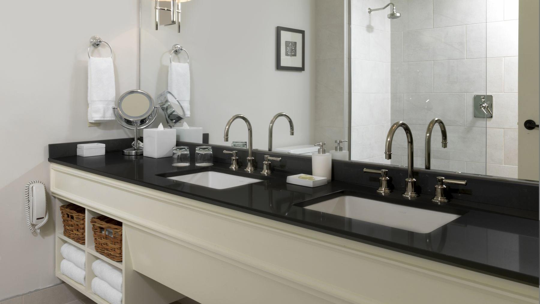 Hotel suite bathroom with two sinks.