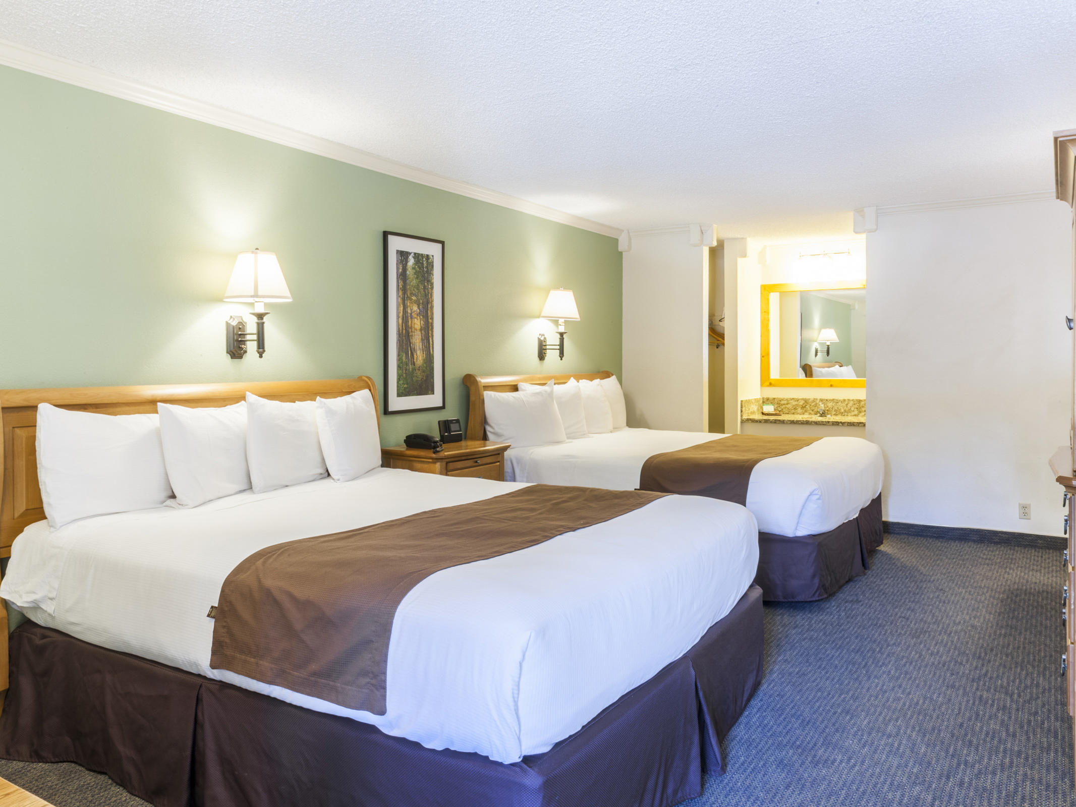 room with two large beds and wall sconces