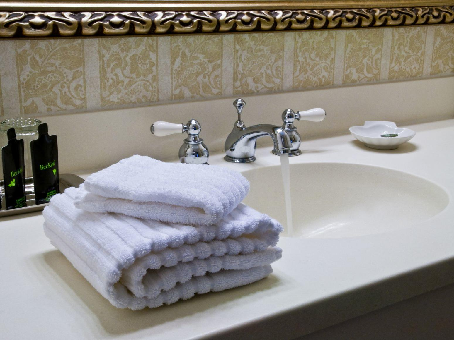 Folded towels and bath amenities next to bathroom sink