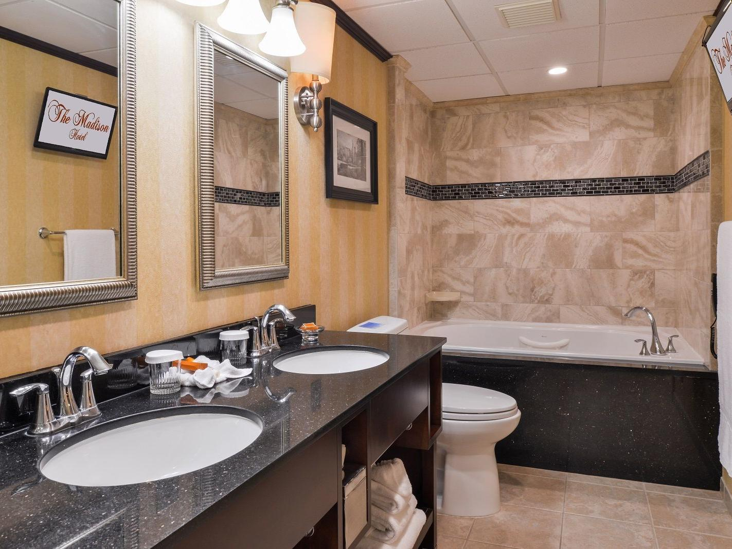 Spacious suite bathroom with two sinks and tub