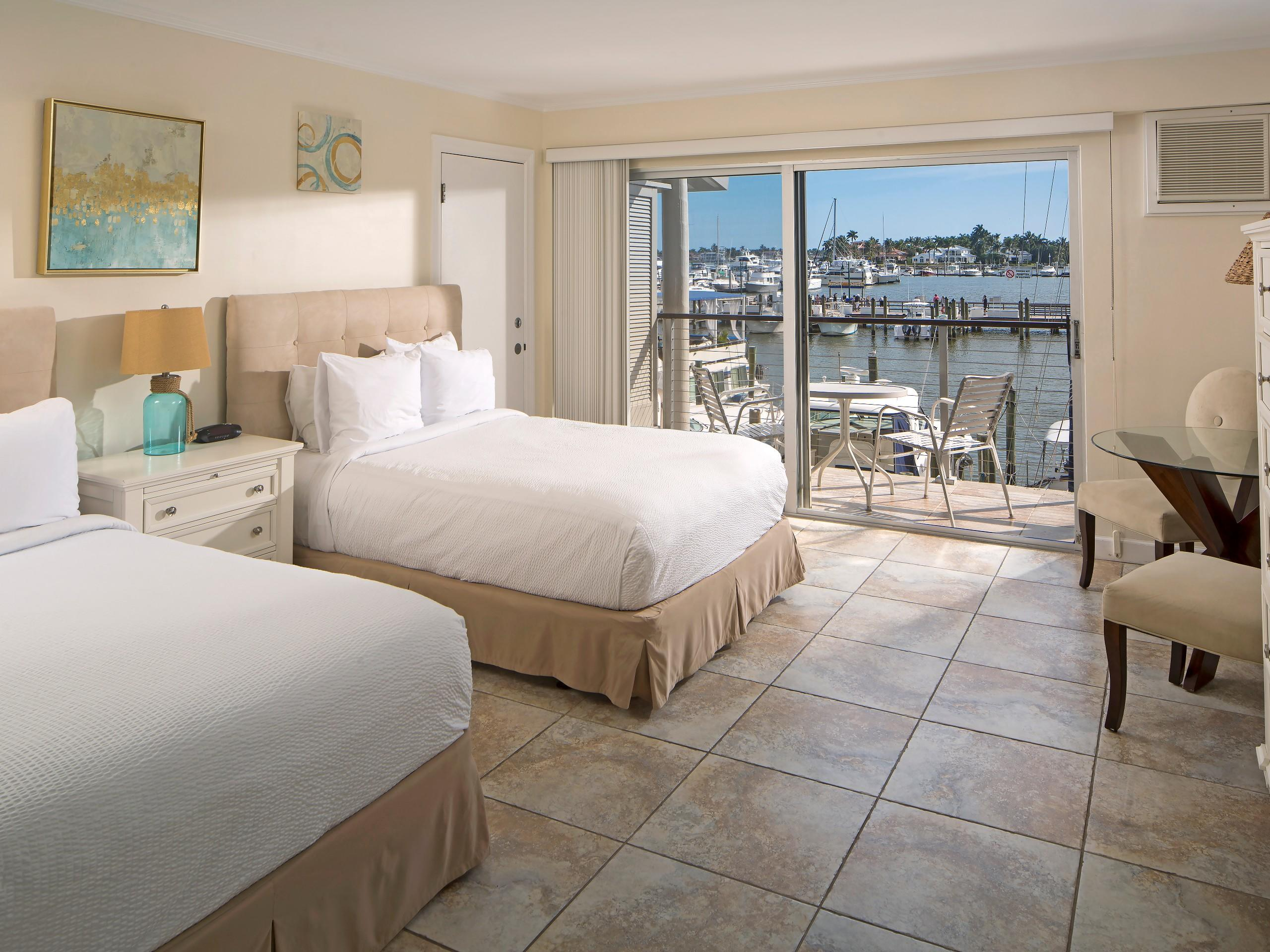 Guest room with two double beds and balcony.