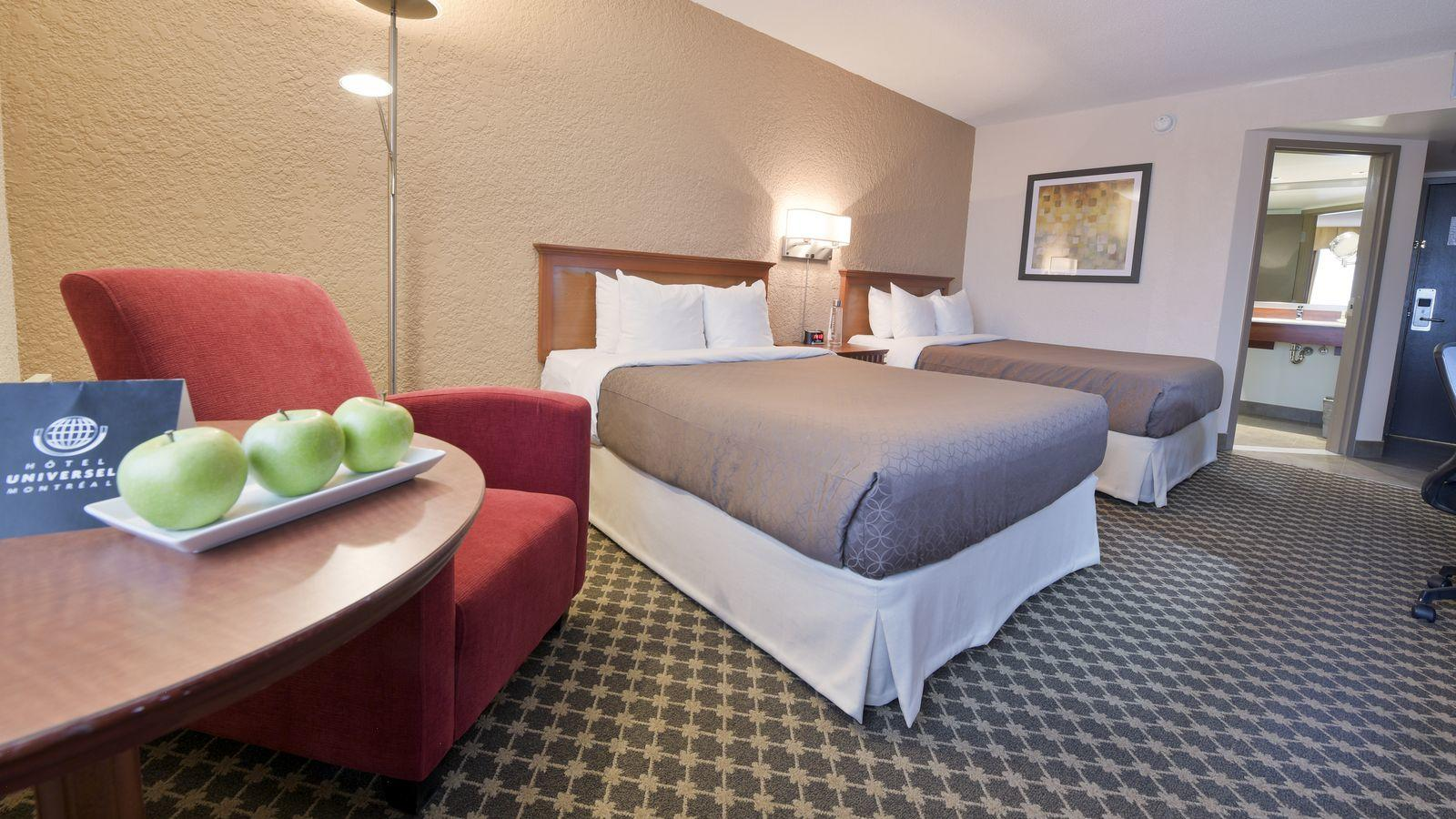 Guest room with two beds, reading chair and table with plate of apples.