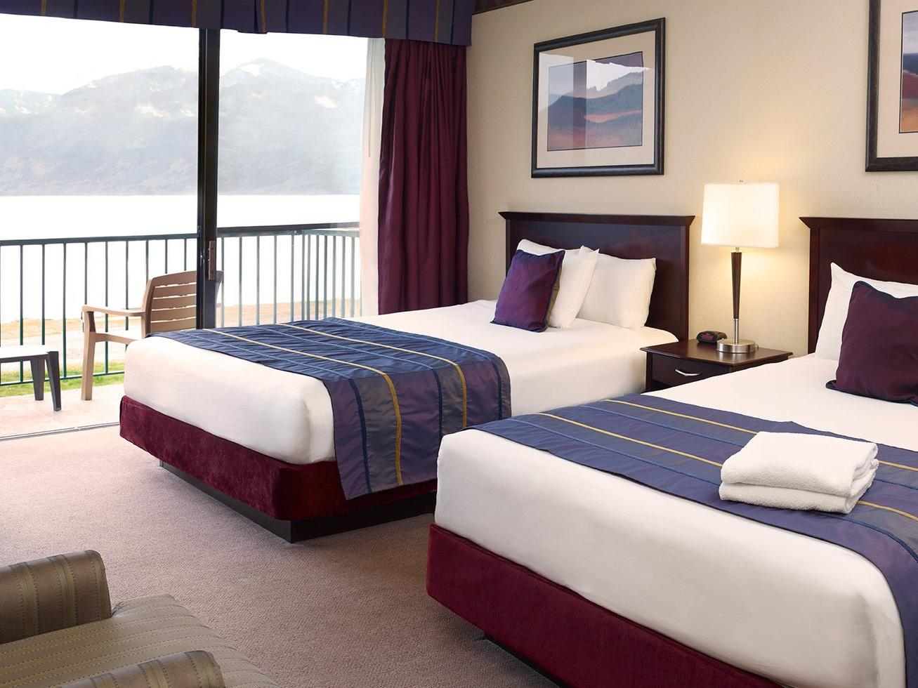 two beds in hotel room with balcony overlooking ocean