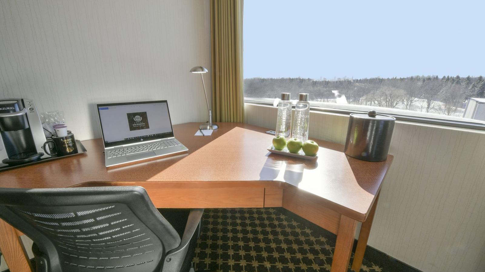 Laptop, bottled water and apples on desk.
