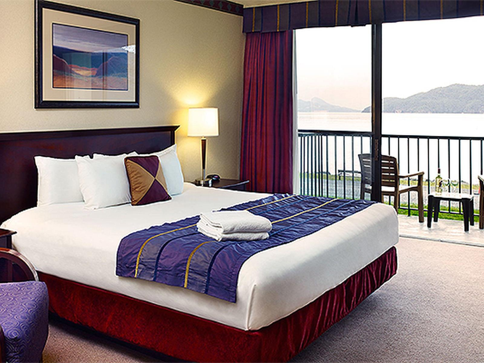 bed in hotel room with balcony overlooking ocean