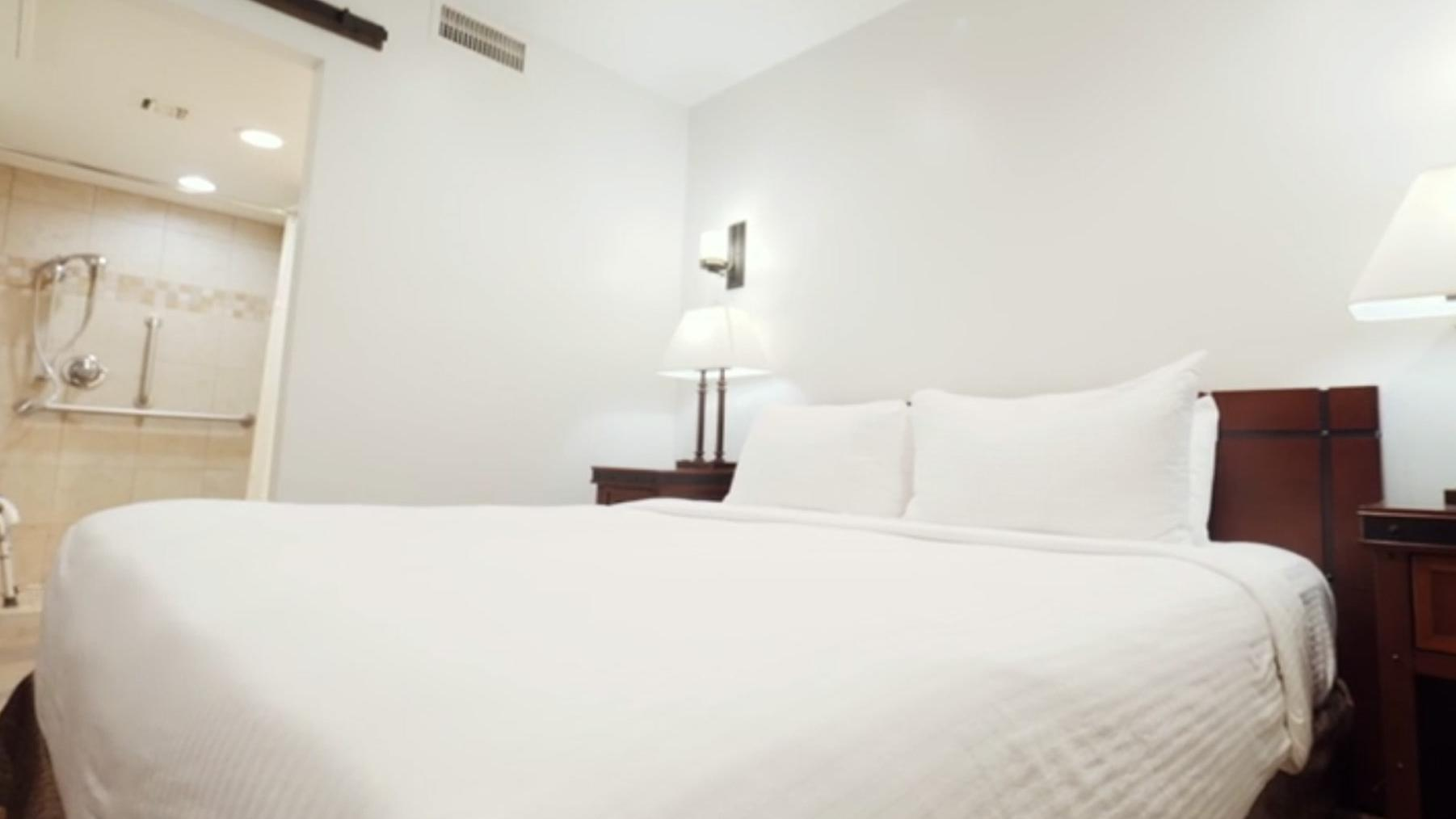 Hotel room with king-size bed with white sheets and standup shower