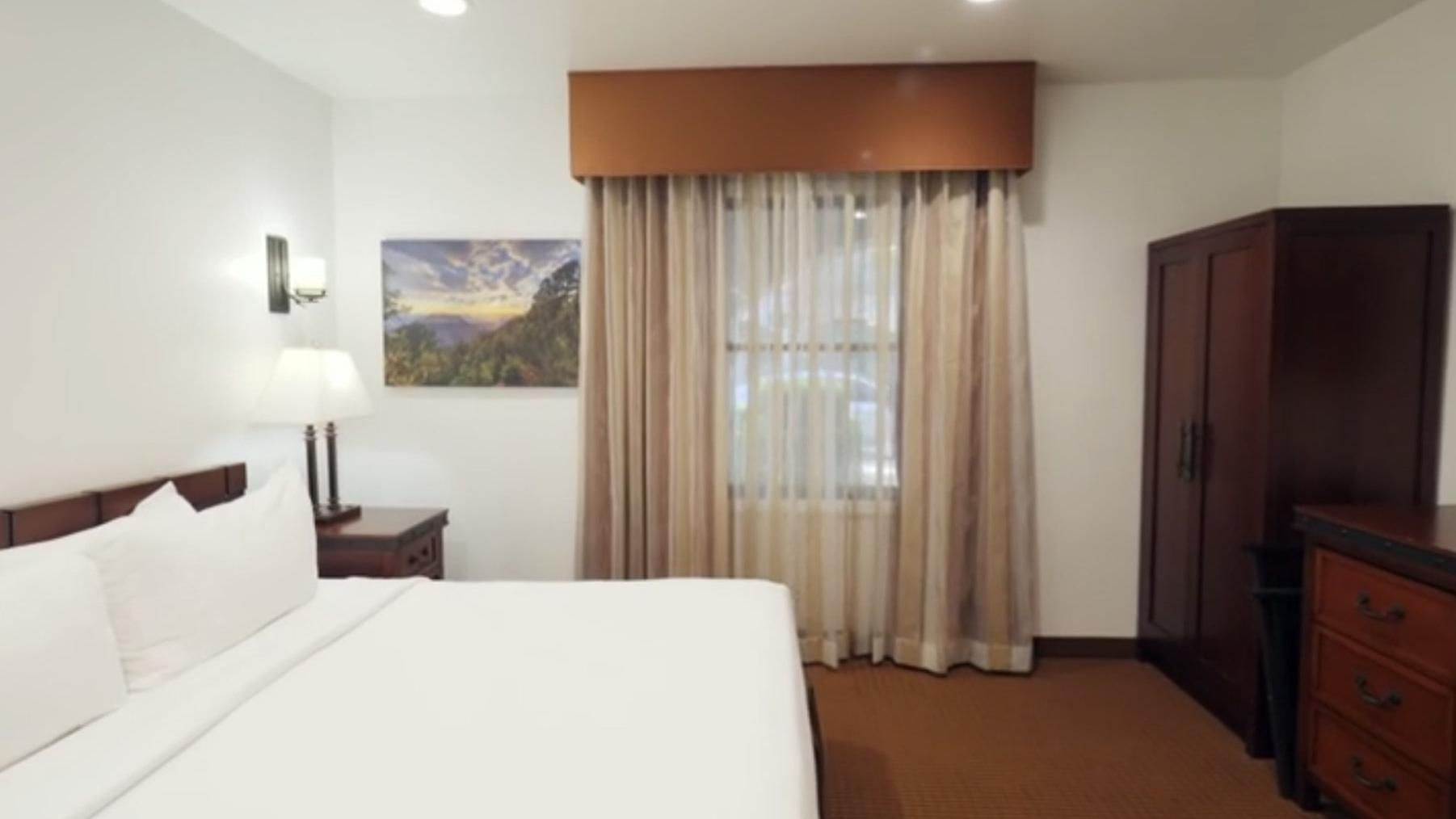 Neutral-colored Sedona hotel room with king bed, wardrobe and dresser