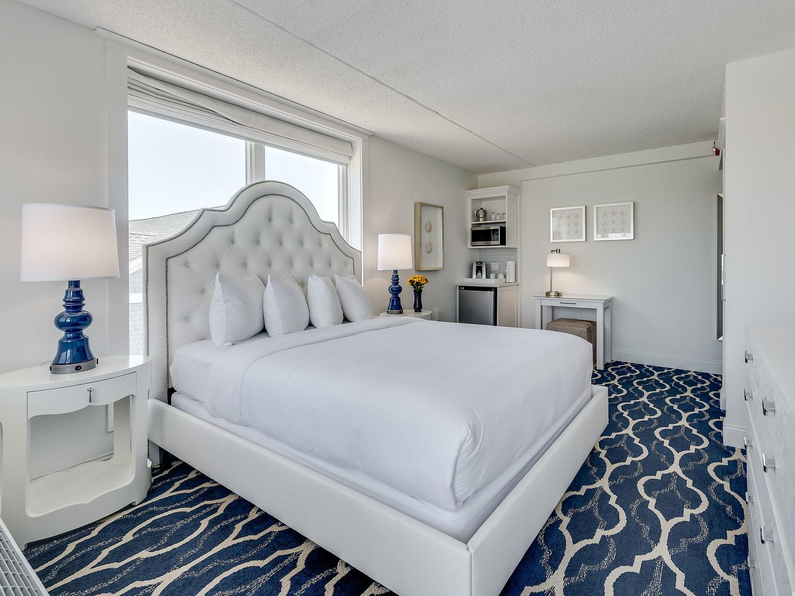 room with all white bed, mini fridge and microwave