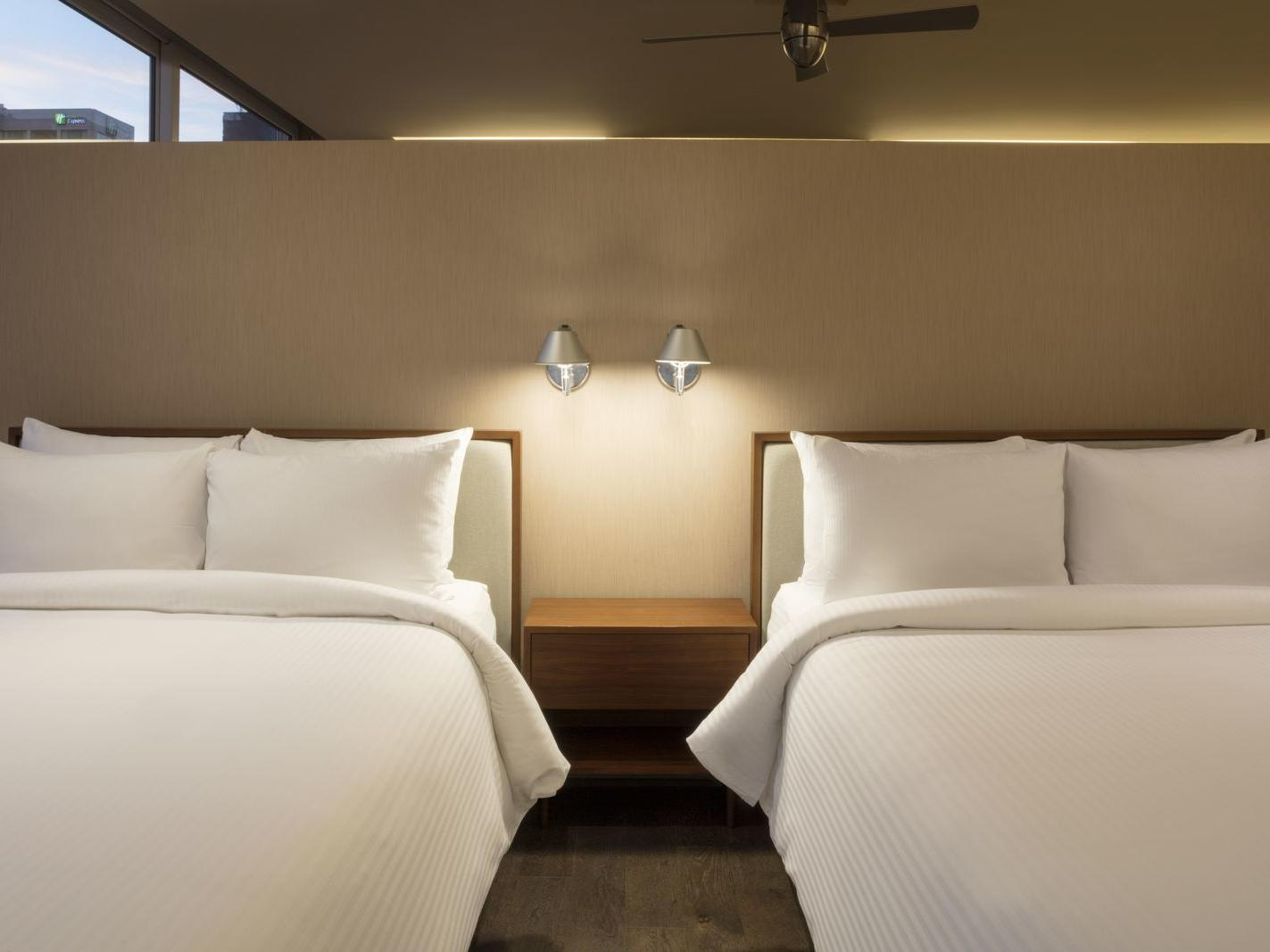 two twin beds with white sheets under night light