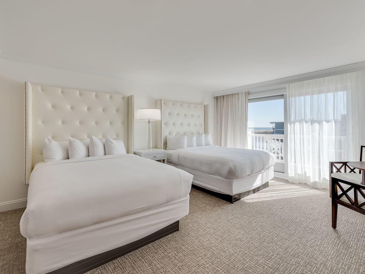 room with two all white beds