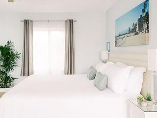 Spacious, white hotel room with Queen bed