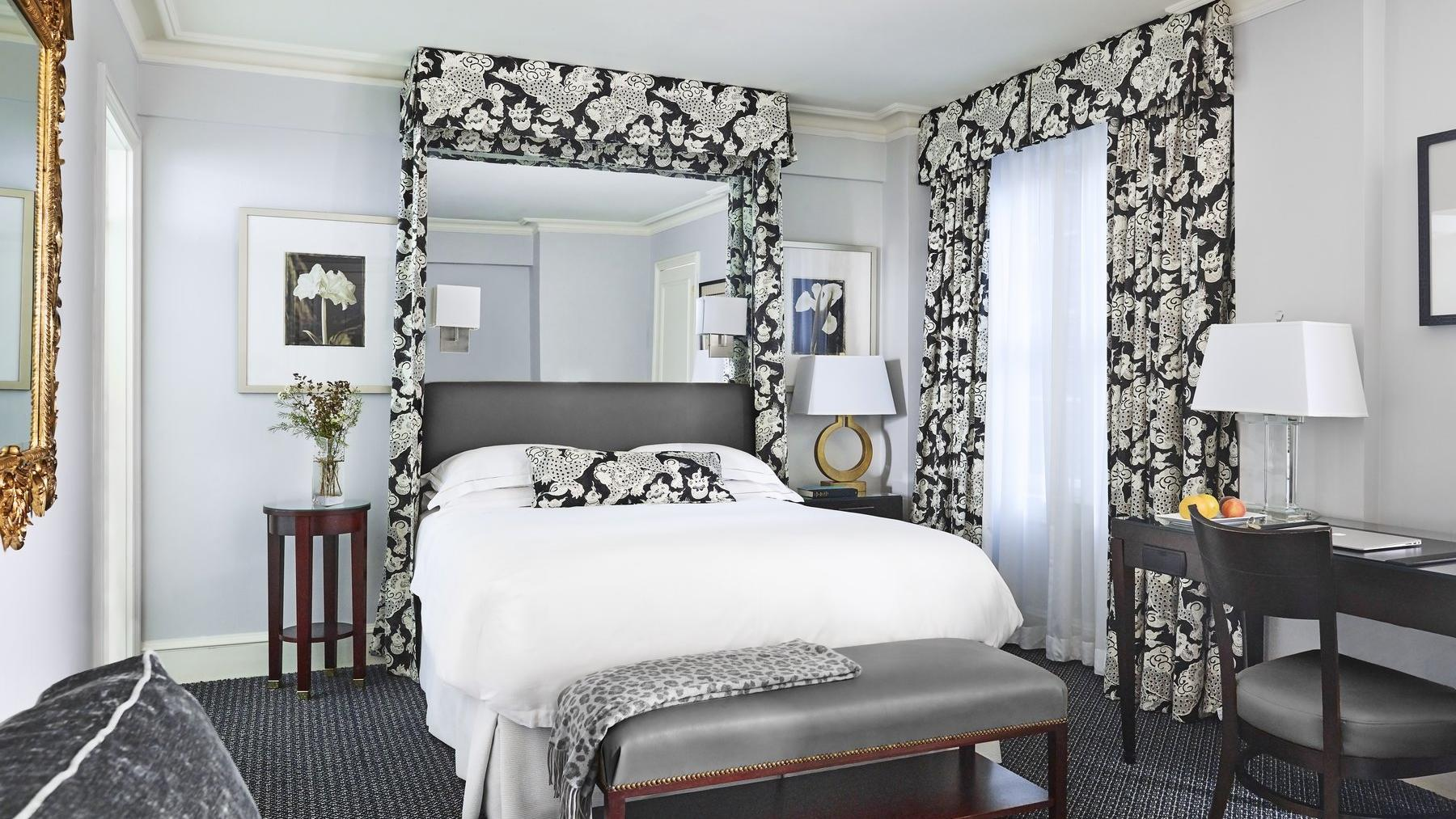 Light grey colored wall room with white queen bed and small desk.