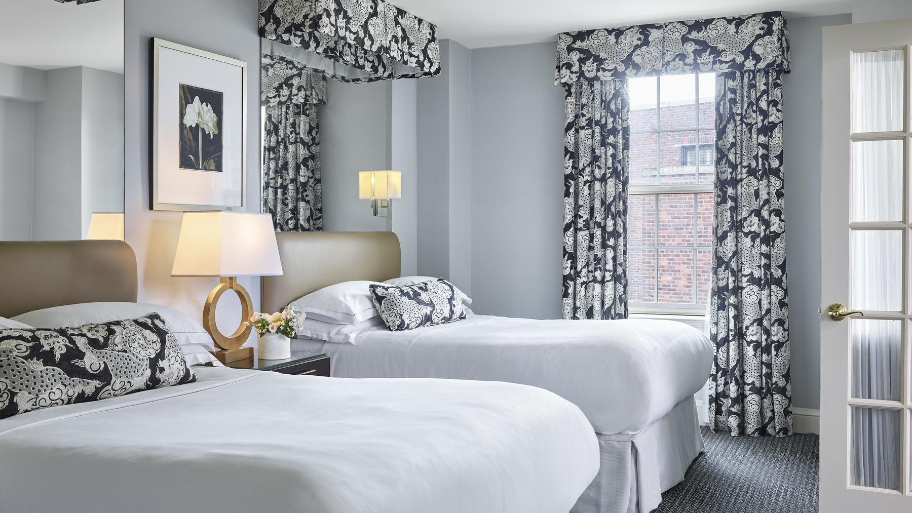Grey colored room with two queen beds and window.