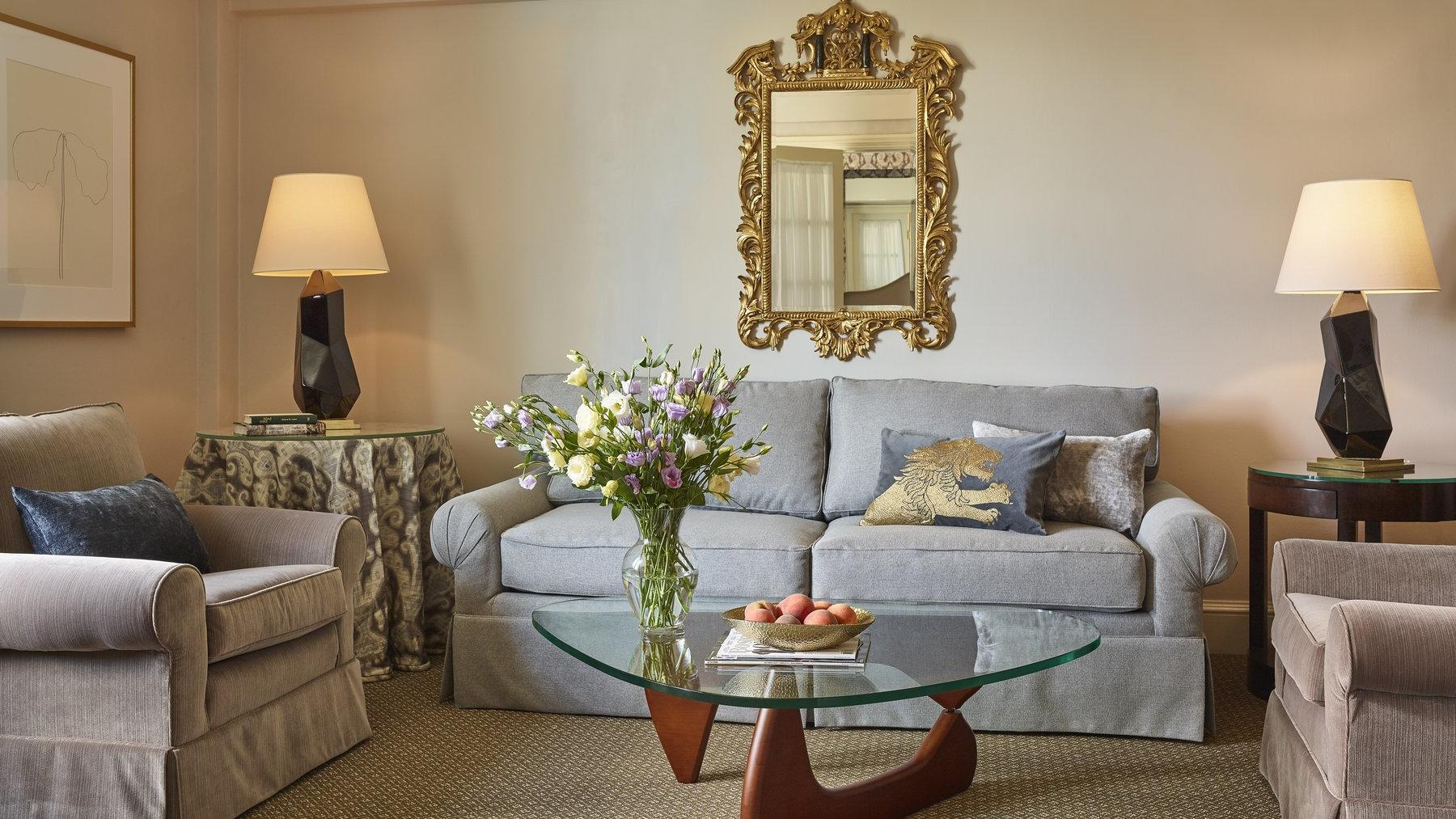 Beige colored living room with grey sofa and taupe accent chairs