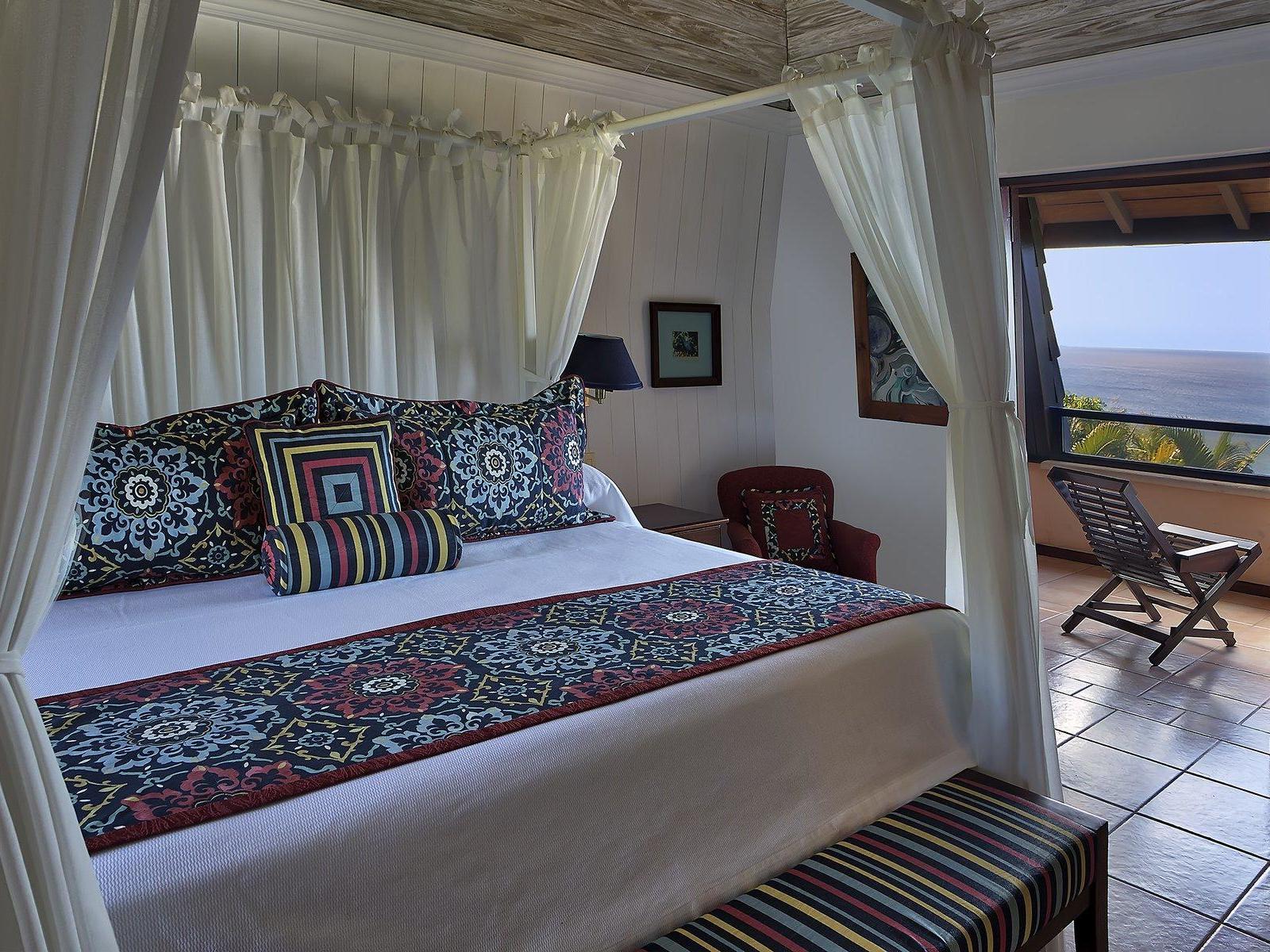 bed in villa with balcony overlooking ocean