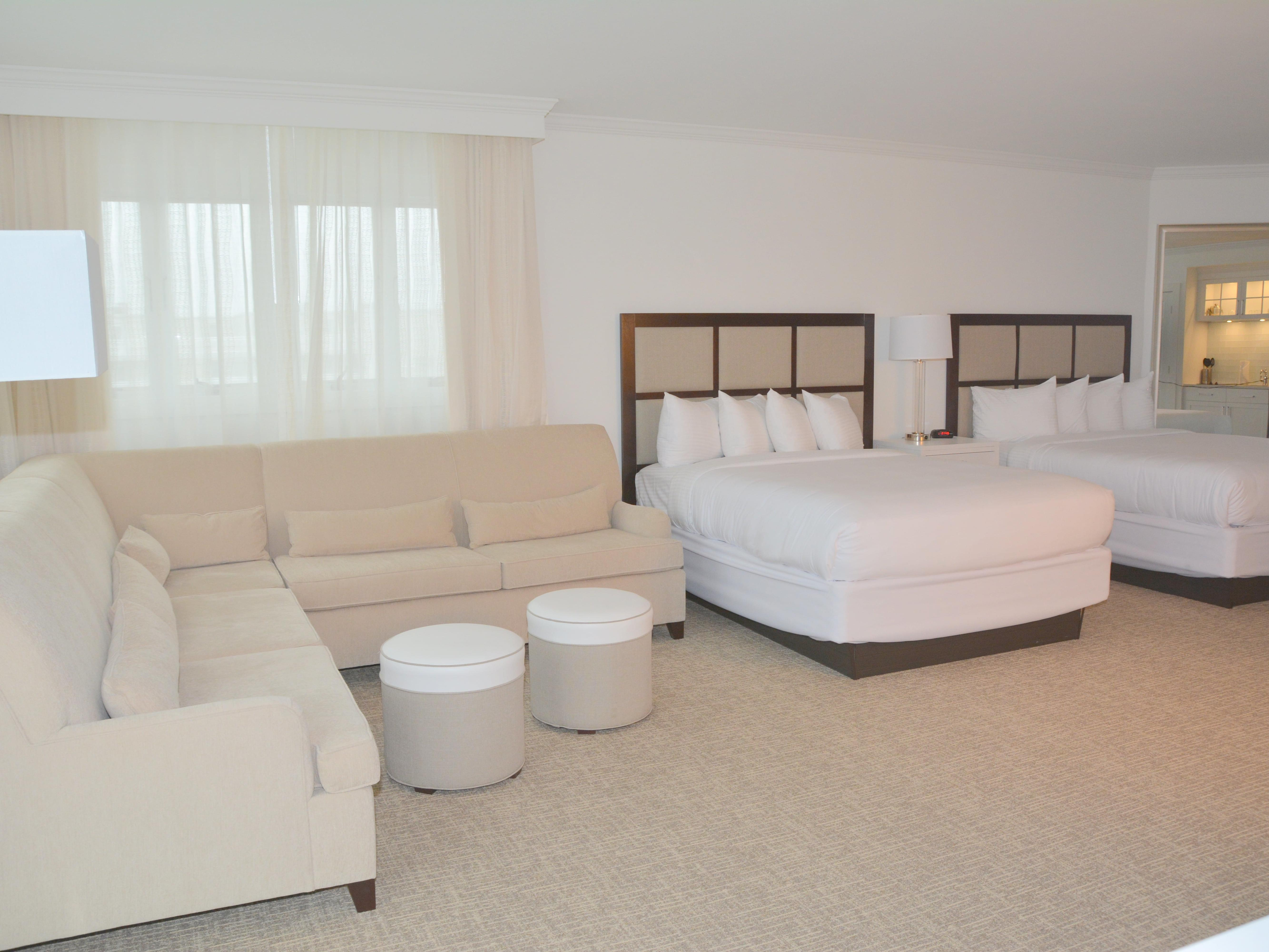 room with two beds and sectional sofa