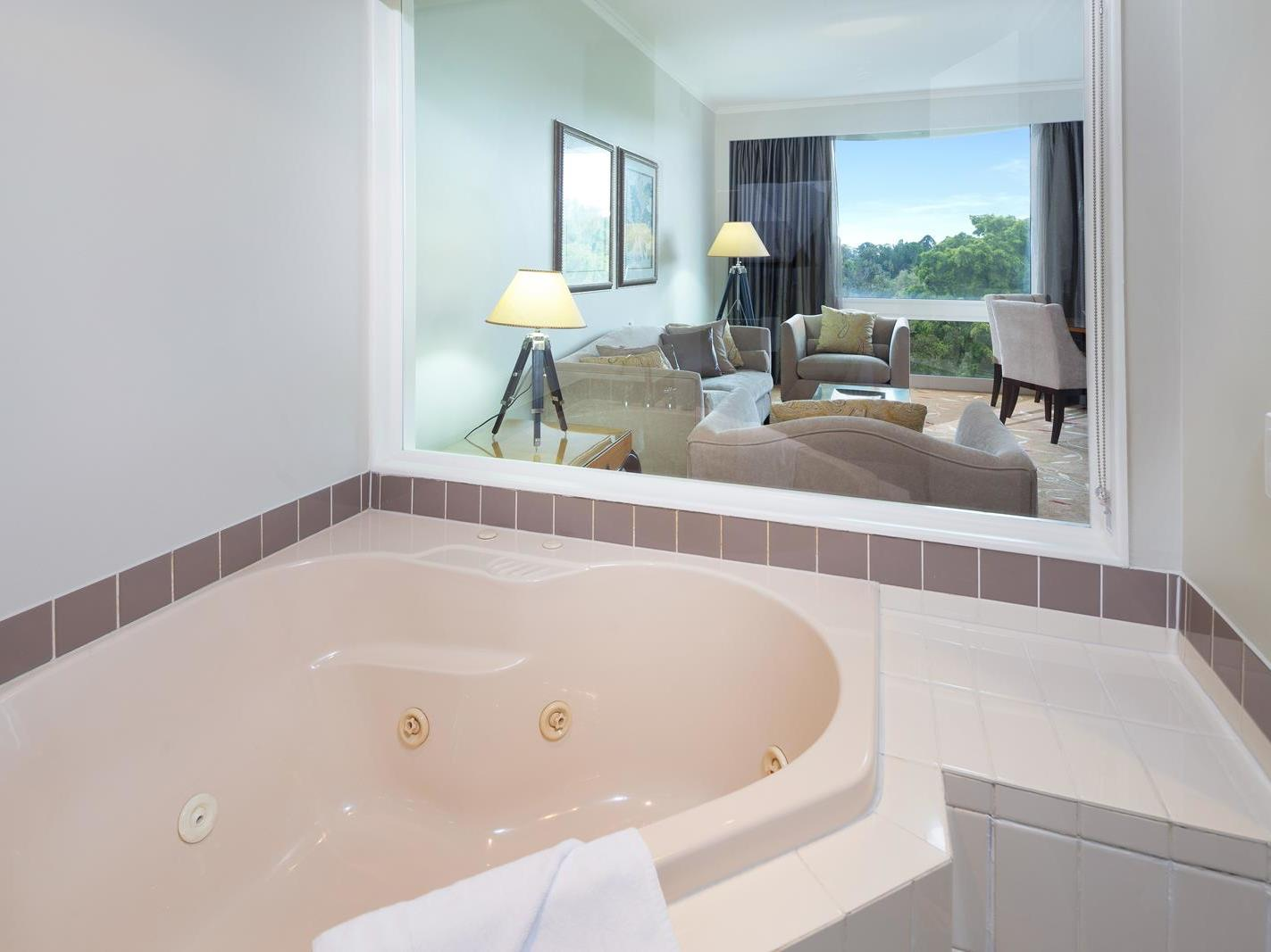 Bathtub with next to the living room with a beautiful view in Deluxe Spa Suite at Royal on the Park hotel