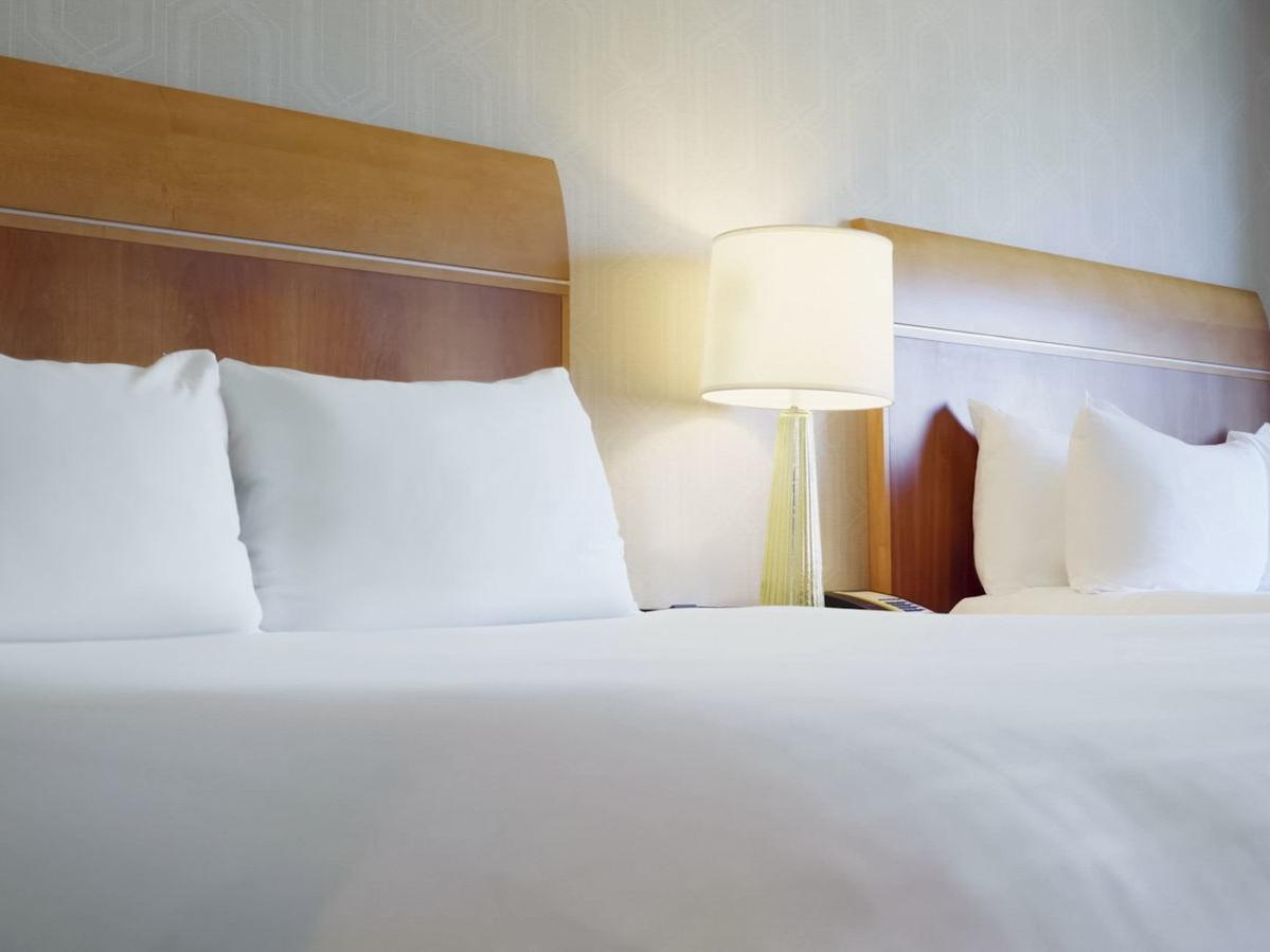 two beds with table lamp in between