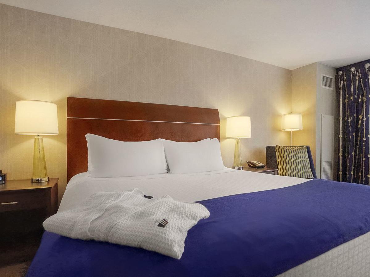bed with white bathrobe folded on the corner