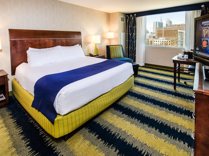 room with bed, yellow and black carpet
