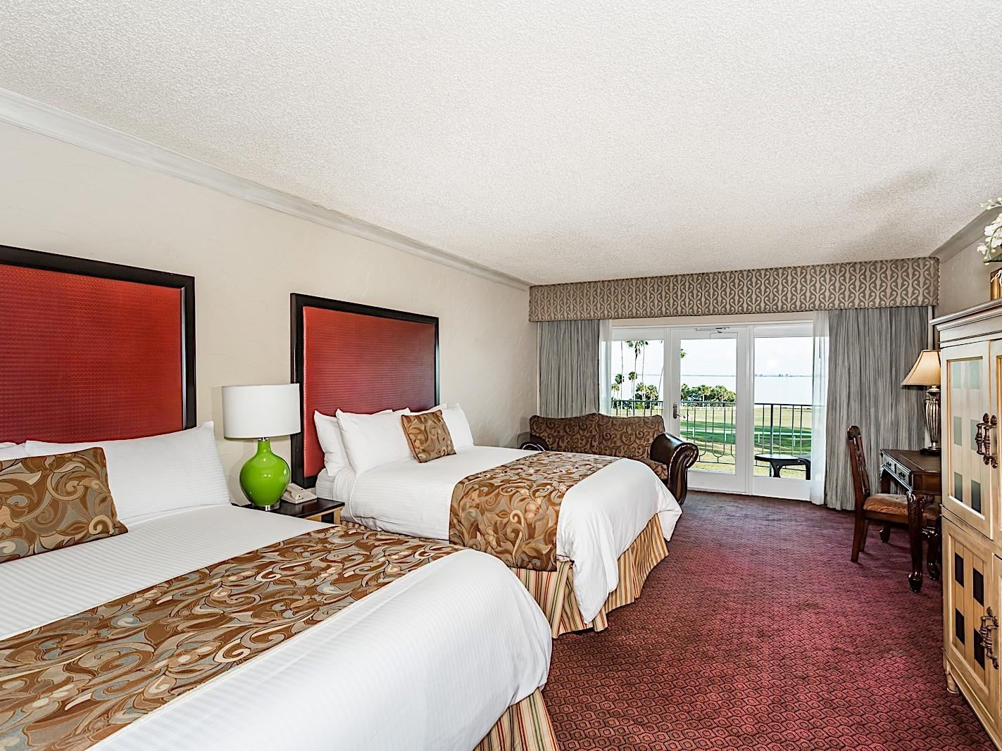 Elegant hotel suite with two Queen beds and pool view.