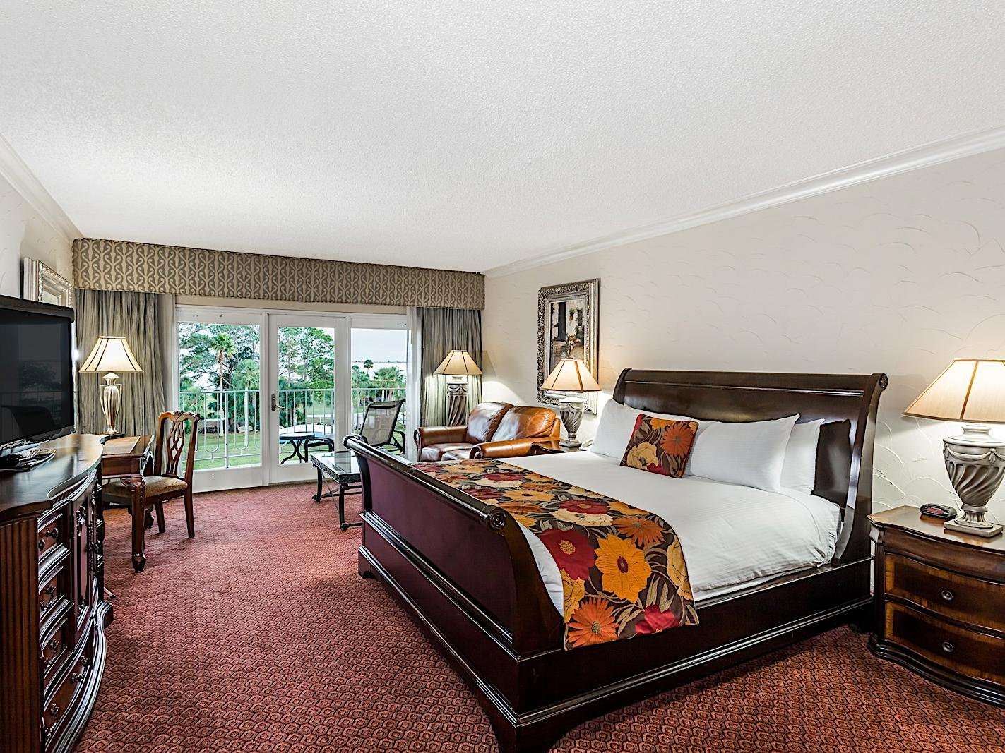 Elegant hotel suite with King bed and pool view.
