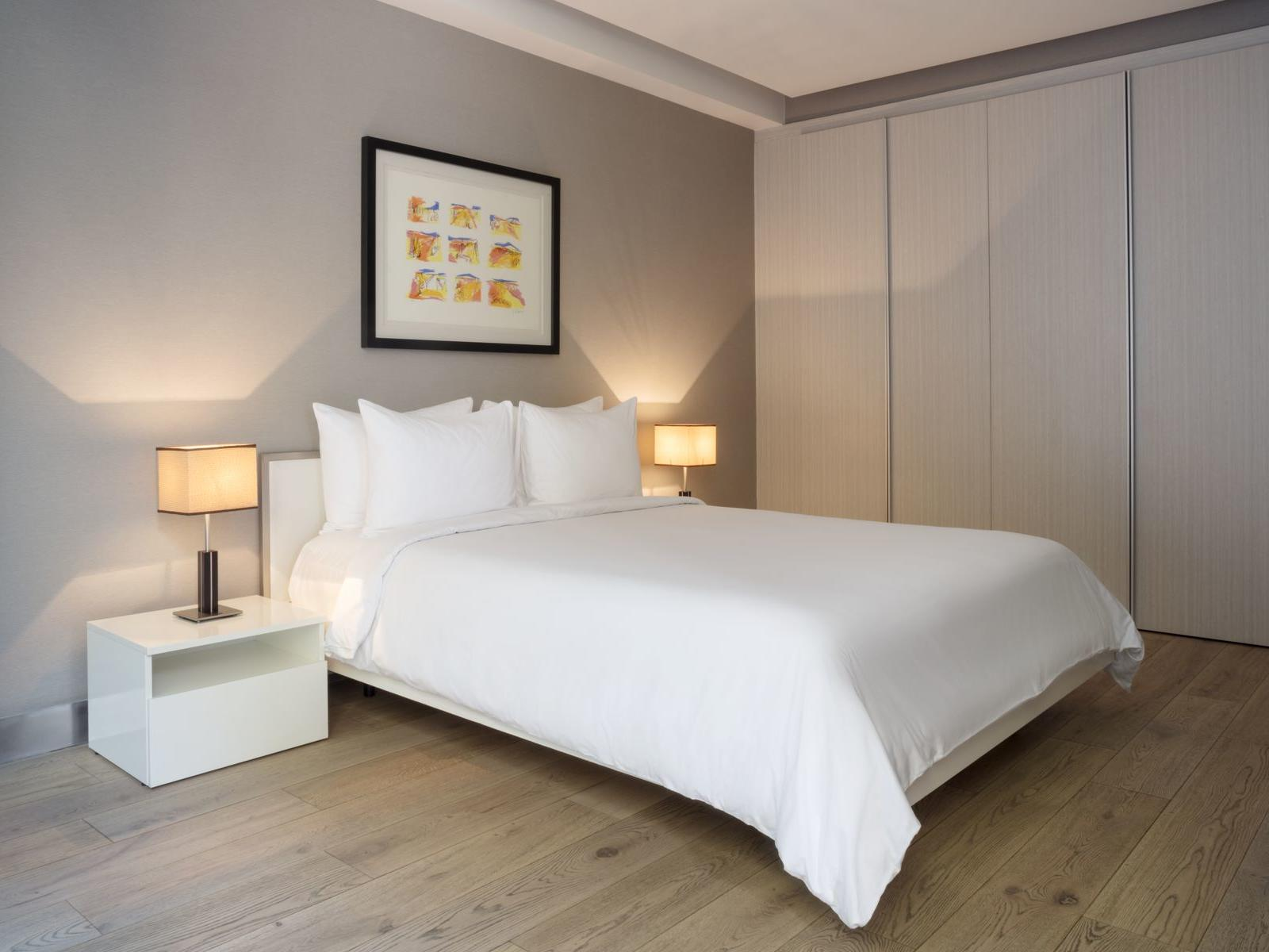 bed with white sheets in cozy room with wooden floors