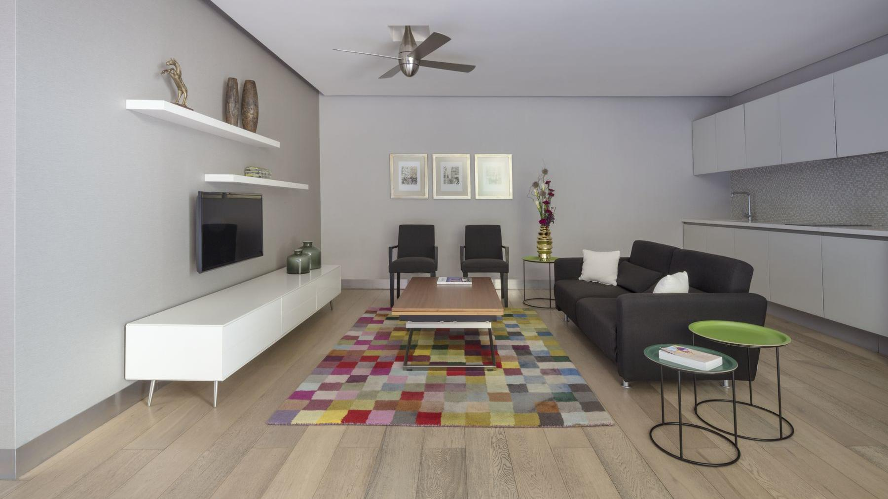 living room area with black sofa, colorful carpet and modern decor