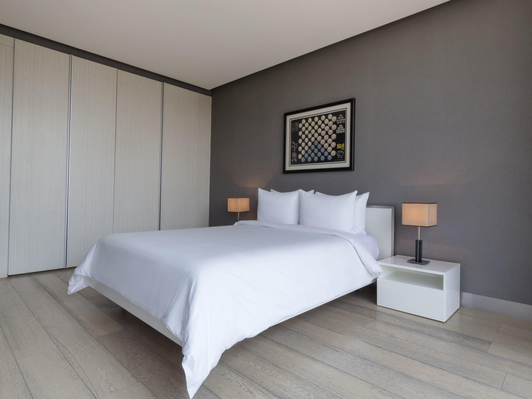 bed with white sheets in large room