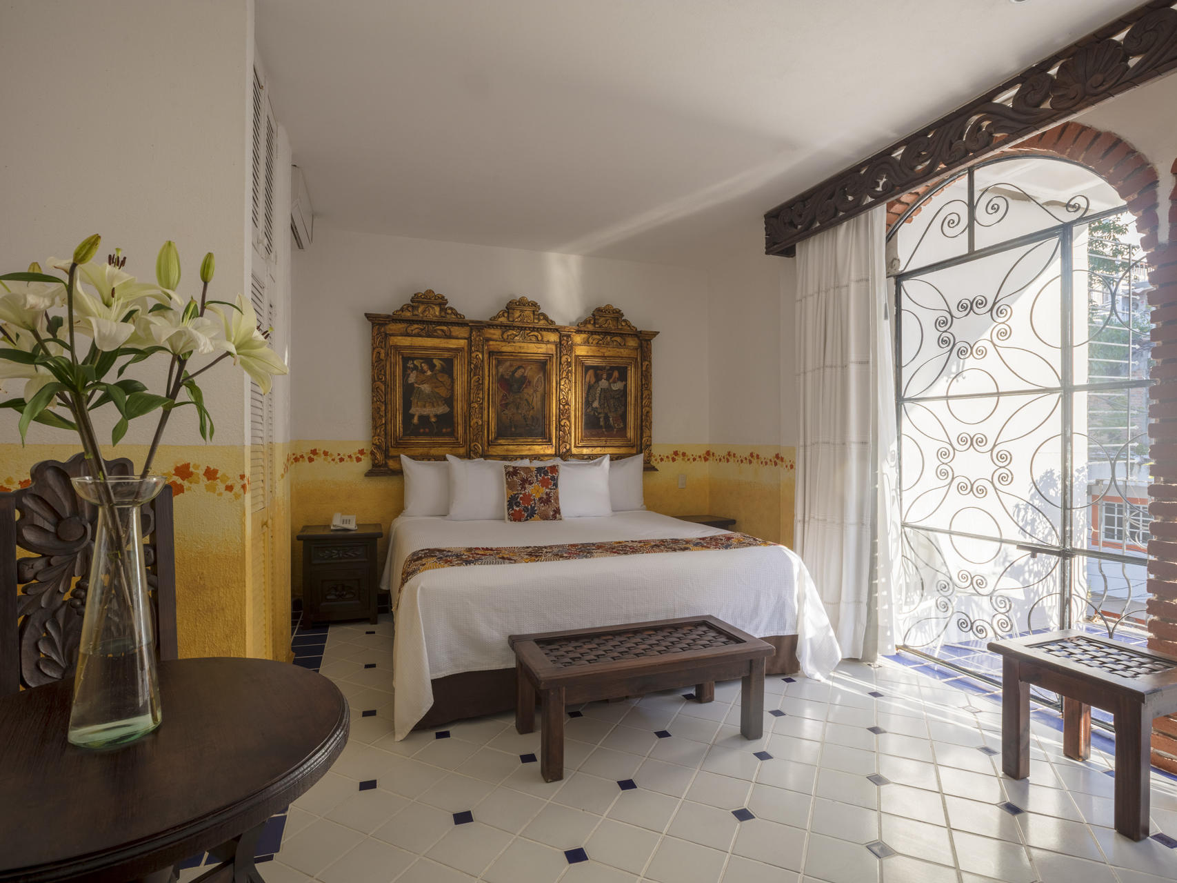 room with one bed, tall windows and table with flowers