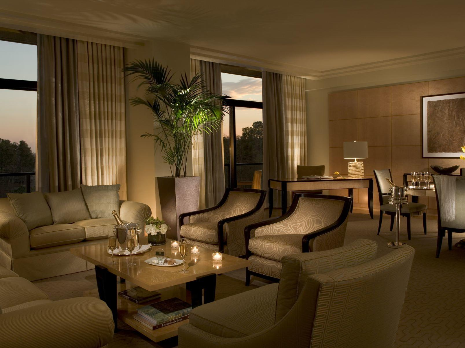 dimly lit lounge area of hotel suite with couches and tables
