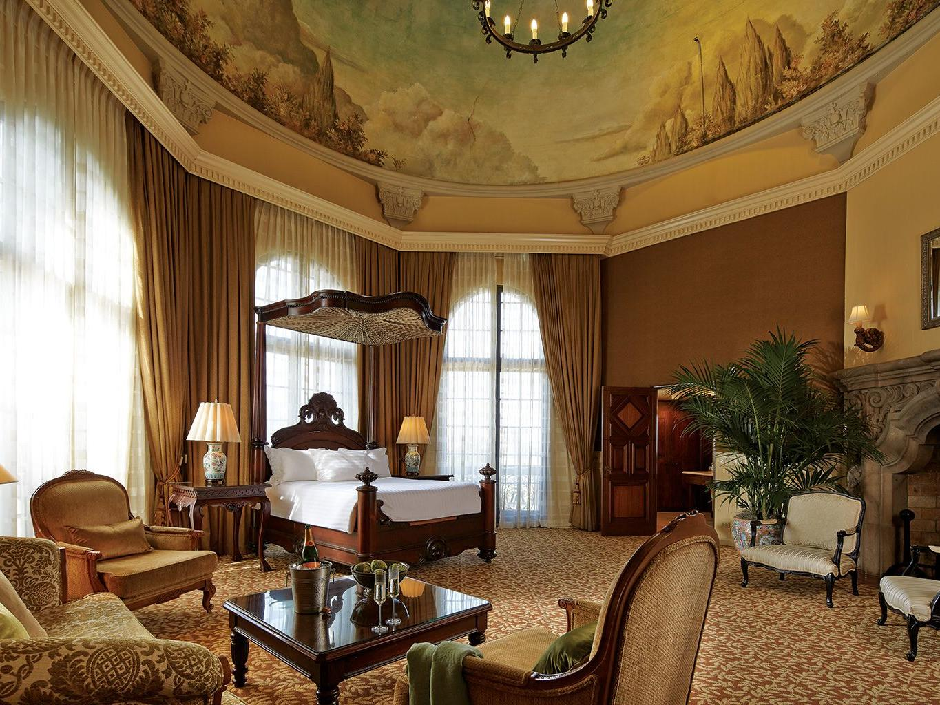 large circular room with canopy bed, seating area and fireplace