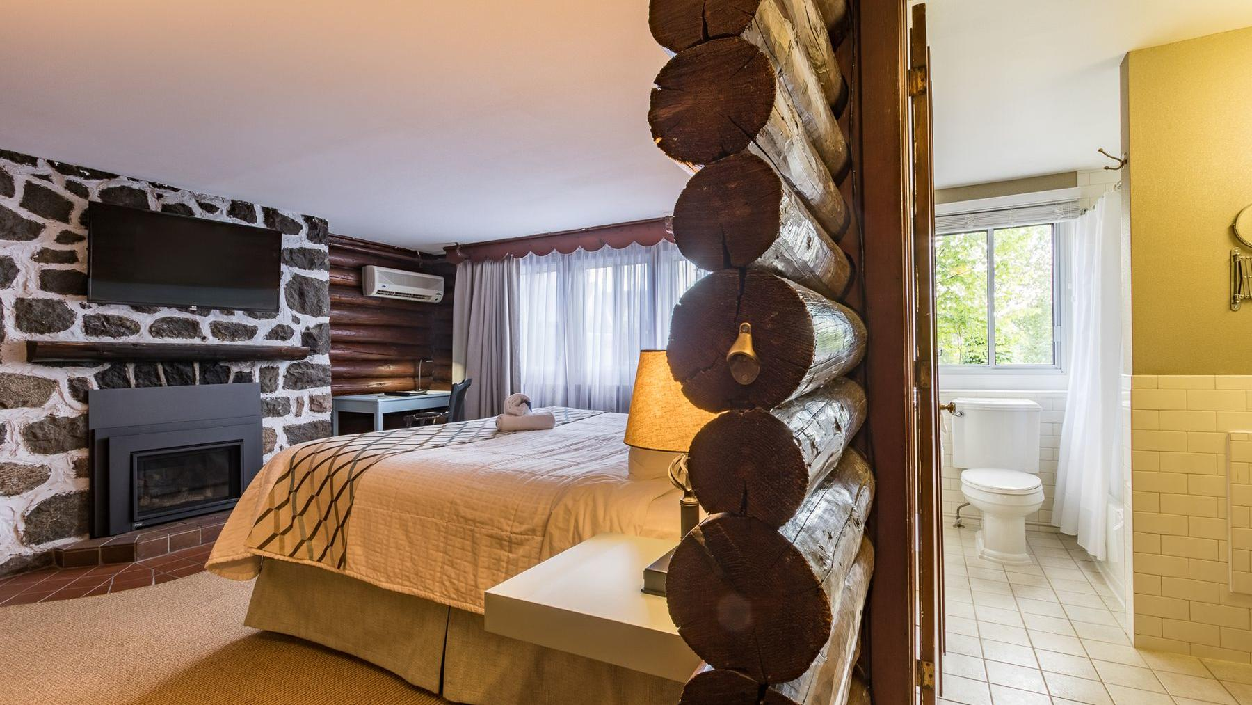 A wall made of logs divides a modern bathroom and bedroom in a hotel
