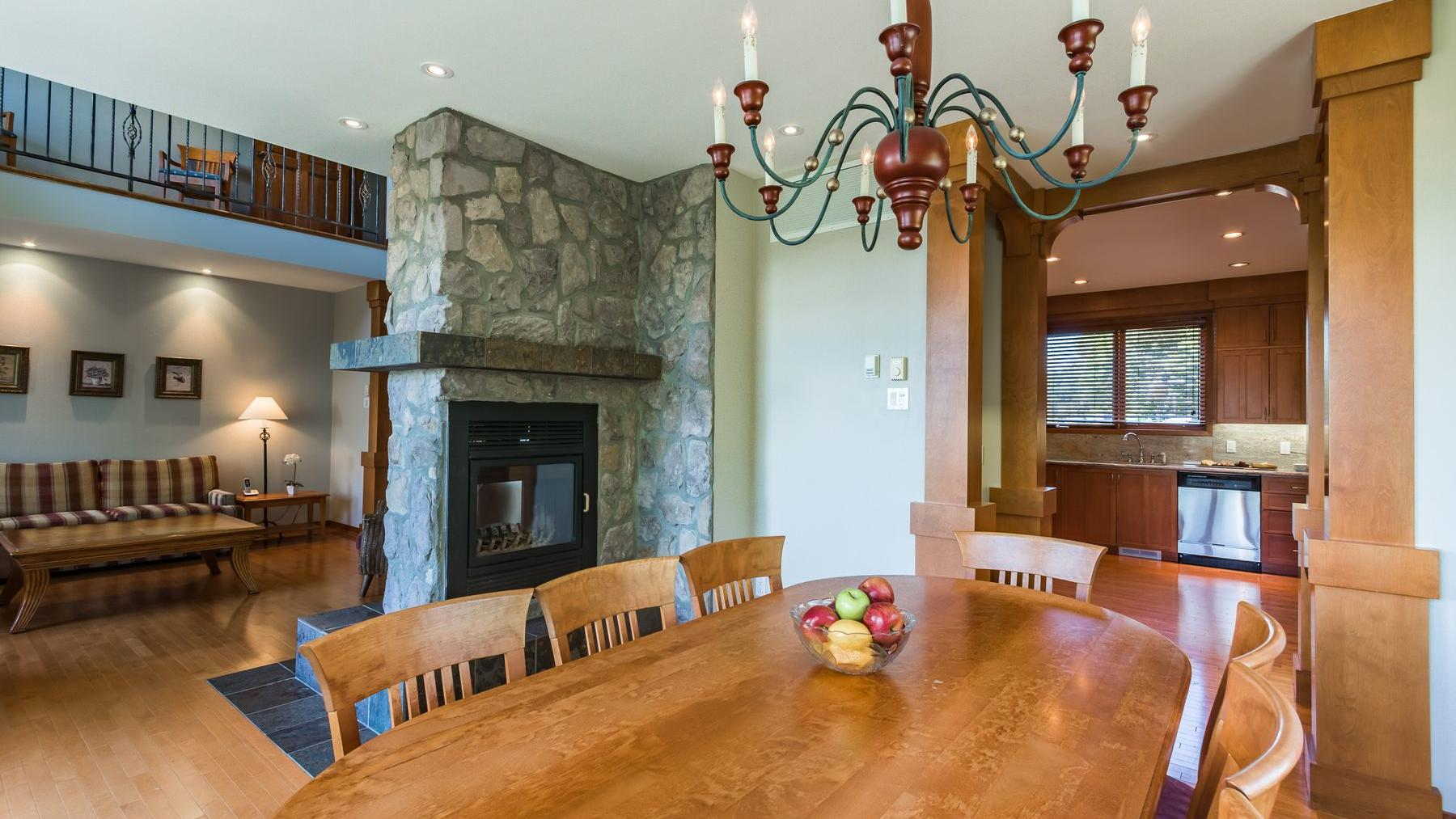 Large dining table and view of kitchen in presidential chalet
