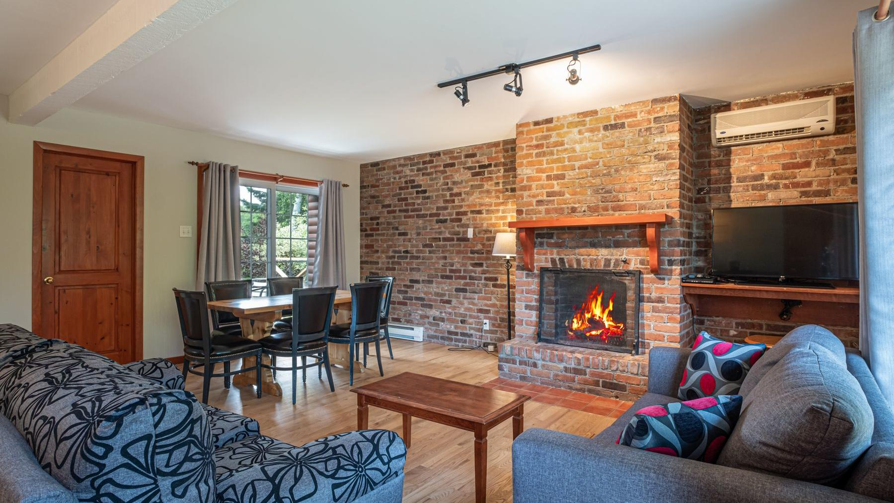 Living room with fireplace, comfy couches, and dining table