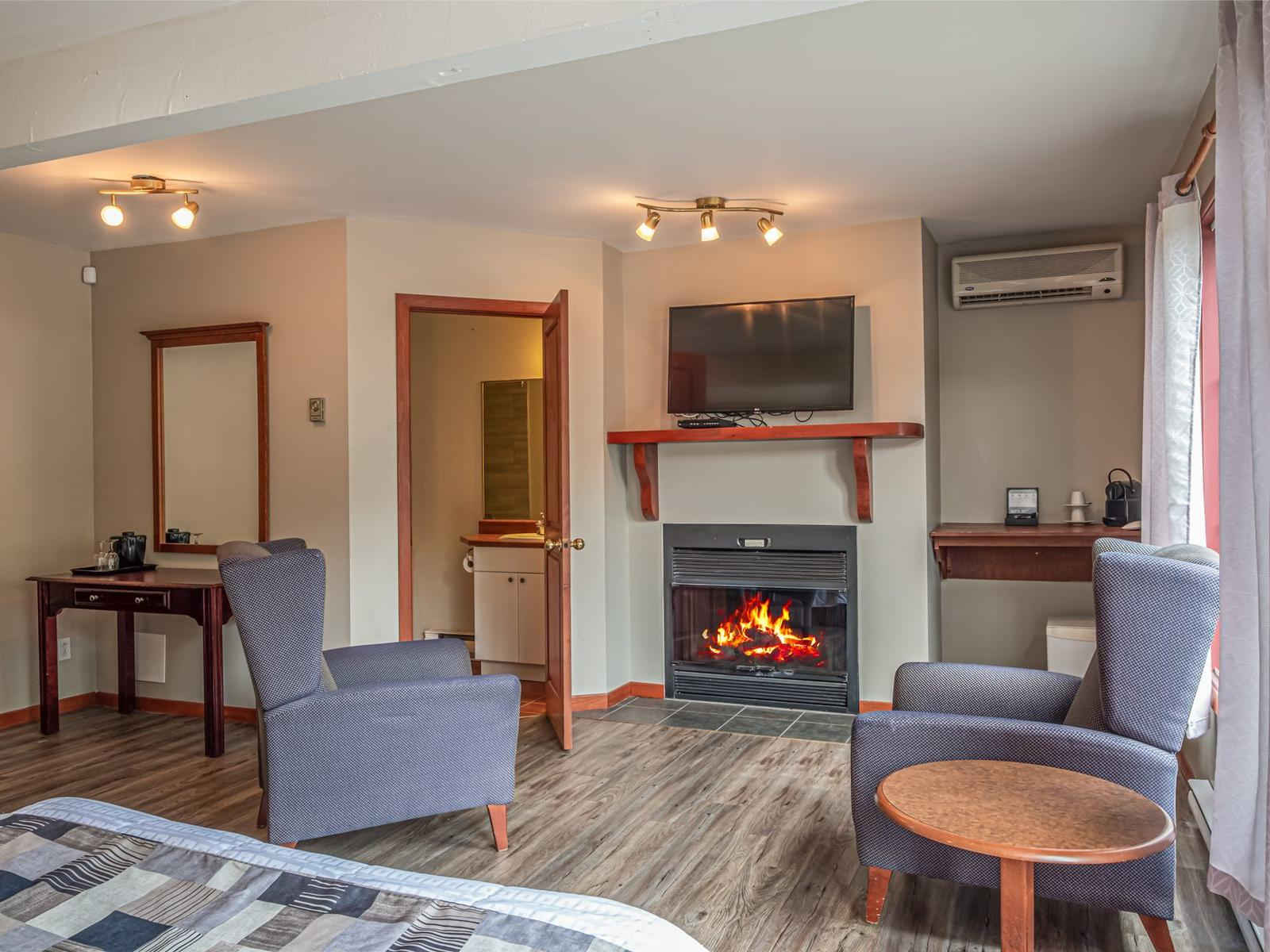 Two chairs and a fireplace in a hotel room