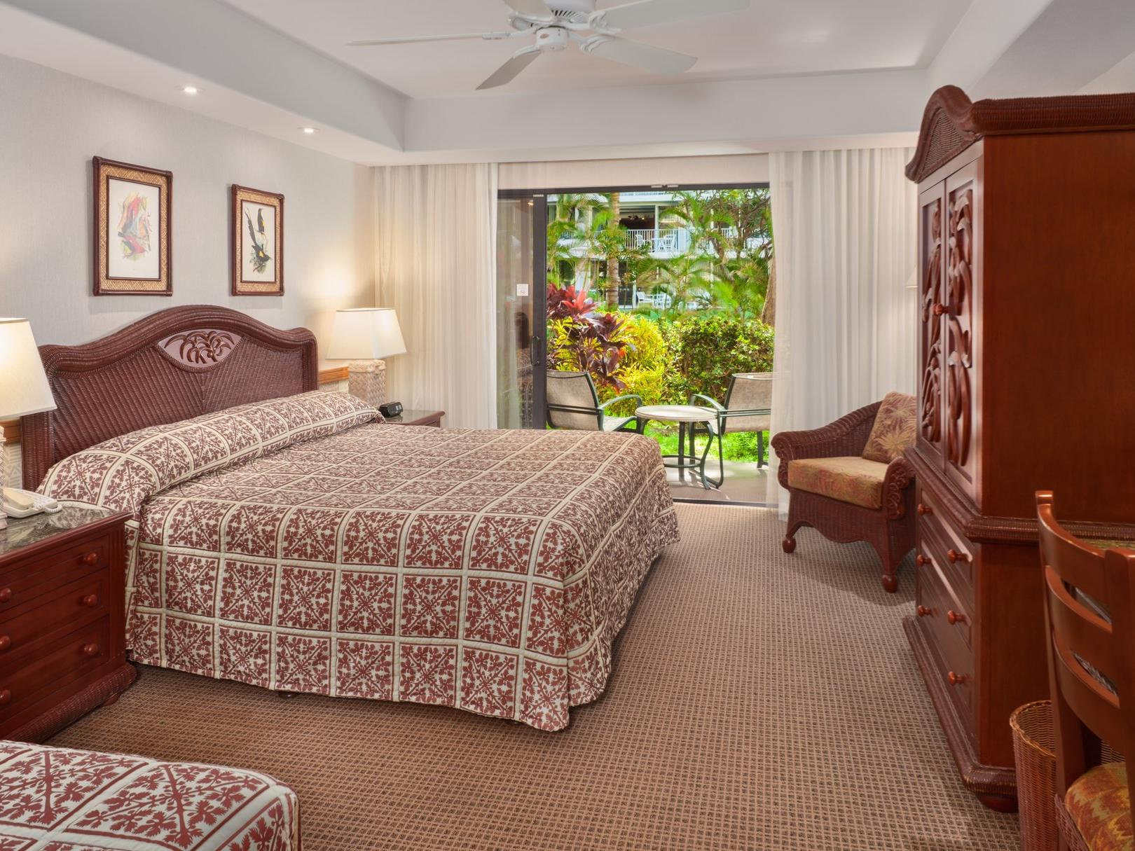 two beds in hotel room with view of tropical setting