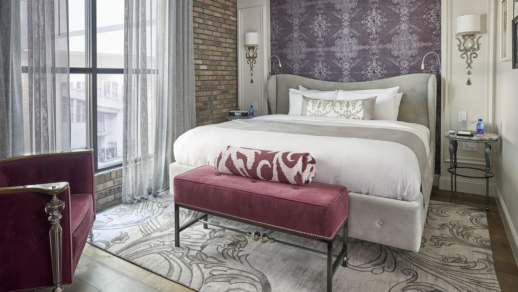 bed in cozy room with carpet and floral headboard