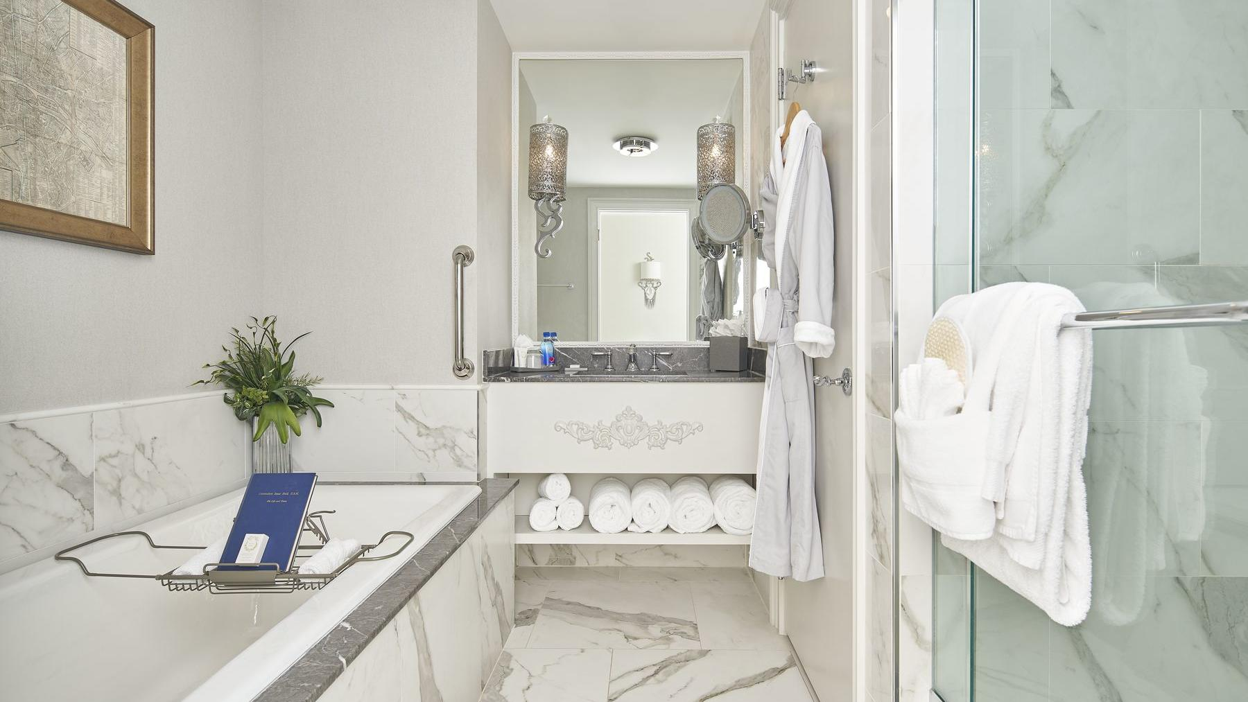 white marble bathroom with mirror, sink and shower
